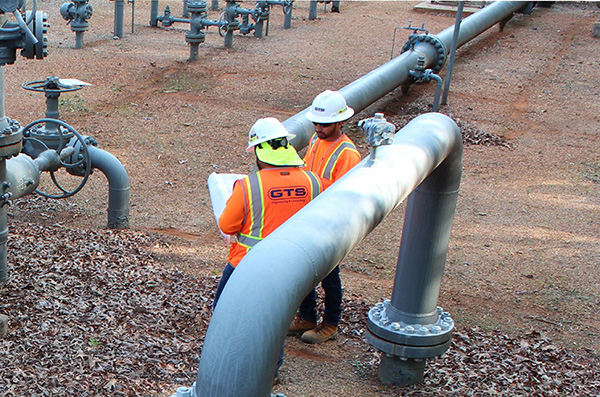 Two engineers reviewing checklist around natural gas station pipelines