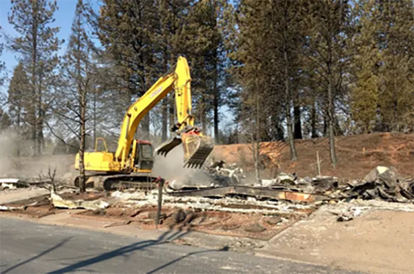 Excavator moving building rubble