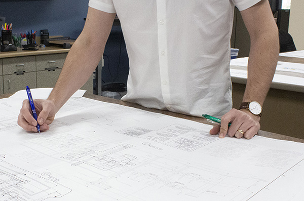 Engineer reviewing drawing holding pen and pencil at table