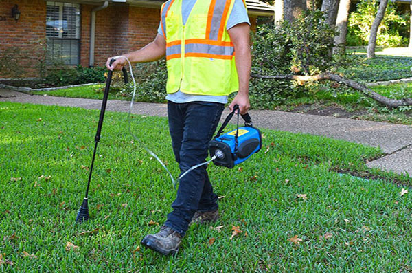 Someone using gas leak detection technology on lawn